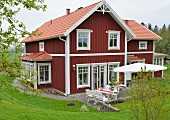 Falu red and white Swedish wooden house with terrace situated in lush, green landscape
