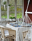 Wicker chairs at set table and hammock chair on wooden veranda