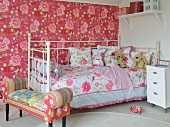 Opulent patterns of roses on wallpaper, bed linen and upholstered bench in girl's bedroom