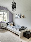 Tray table next to bed in girl's attic bedroom with white and pale lilac walls