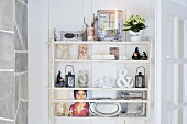 White shelves decorated with candles, trays and pictures in Scandinavian wooden house