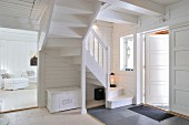 Foyer with winding wooden staircase and view into living room in wooden house painted entirely white and with white furnishings