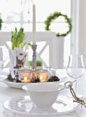 Place setting on dining table; bowl with handle decorated with cord, glass plate, wine glass and centrepiece on plate in background