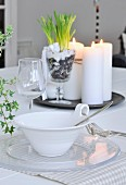 Place setting on dining table; bowl with handle decorated with cord, glass plate, wine glass and arrangement of candles and plants on tray