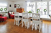 Scandinavian, country-house-style interior with white-painted dining set, red armchairs and Advent wreaths in windows