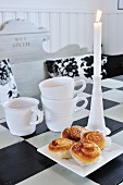 Pastries, candles and cups on old dining table painted with black and white chequered pattern
