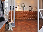 Tiled hallway with glass partitions; view of decorative letters on vintage apothecaries' cabinet