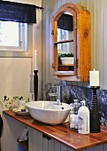 Rustic mirrored cabinet above washstand with varnished beach worksurface and stone splashback
