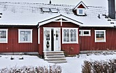 Falu-red, Scandinavian wooden house with snowy roof and decorated front door on projecting porch