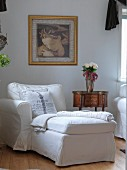 White chaise in front of antique, delicate side table below gilt-framed painting on wall