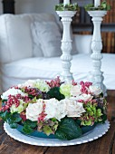 Wreath of white roses and berries on table in front of white ceramic candlesticks
