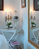 Multi-armed, brass candelabra and decorative glass container on white tray table in corner