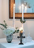 Lit candles and cross in front of crystal carafes on table with white tablecloth