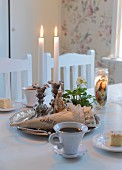 Coffee, slices of cake and lit candles in candlesticks on silver tray