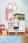 Girl standing in front of dolls' house on cabinet in child's bedroom decorated in bright colours