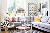 Seating area with patterned, retro scatter cushions on corner sofa, pendant lamp with metal lampshade and Scandinavian side tables