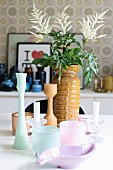 Tealight holders and candlesticks in front of traditional ceramic vase on table
