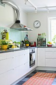 Simple fitted kitchen with retro utensils on grey worksurface and orange rug on grey chequered floor