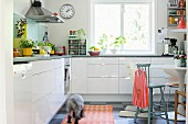 Base units with glossy white fronts in bright, retro kitchen-dining room with various chairs