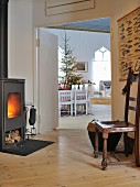 Antique chair in front of wood-burning stove with view through to dining area and Christmas tree in living room