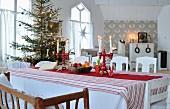Blick von Esstisch mit rot-weisser, skandinavischer Deko auf geschmückten Weihnachtsbaum
