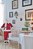 Father Christmas figure, Swedish festive greeting on armchair and old pictures on wood-panelled wall