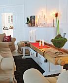 Polstermöbel und Vintage Tisch aus alter Werkbank und Schubladenschrank; weihnachtliche Deko mit Kerzen und Amaryllis-Gesteck