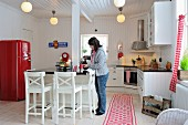 White, Scandinavian, country-house kitchen with red, retro fridge and woman pouring drinks at breakfast bar
