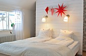 Attic bedroom with storage space behind partition headboard and reading lamps and red Christmas decorations above bed