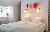 Schlafzimmer unterm Dach mit Stauraum hinter einer Rückwand mit Wandleuchten und roter Weihnachtsdeko