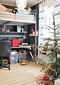 Teenager's metal loft bed with integrated desk; Christmassy curtains with printed lettering and Christmas tree in foreground