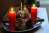 Lit candles and fir cones on stainless steel tray on table with figurines of three wise men in background