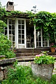 View from garden of climber-covered summer house with wooden steps leading to open terrace doors