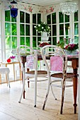 Thonet chairs with white, peeling paint around table in conservatory with floor-to-ceiling lattice windows