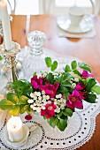 Gartenstrauss und Kerze auf Spitzendeckchen