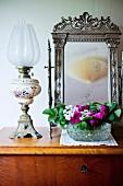 Petroleumlampe und Blumenschale, vor Standspiegel mit verziertem Silberrahmen, auf schlichter Holzkommode