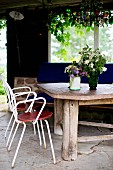 White, delicate metal chairs at rustic wooden table with vases of flowers on stone loggia floor