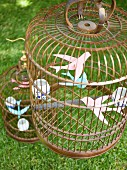 Paper birds in birdcage as decoration for summer garden party