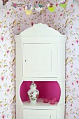 White, rustic corner cabinet with carved pediment against vintage-style floral wallpaper