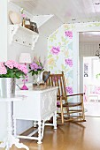 Wooden rocking chair next to flowers on white, ornate cabinet