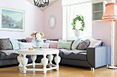 Round, white coffee table with carved base in front of corner sofa against pastel pink wall