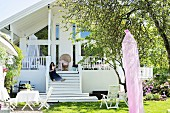 Sunny garden with seating area, woman sitting on steps leading to modern, white country house