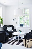 Seating area with black armchairs around round table