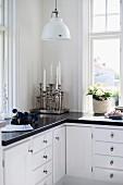 Küchenunterschrank Übereck mit silbernen Kerzenständern; Pendelleuchte im Retrostil