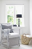 Comfortable, white wicker chair with seat cushion and raffia shopping bag with heart motif in front of black table lamp on windowsill in simple interior