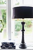 Table lamp with mother-of-pearl sequins decorating black lampshade and turned base in front of window