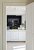 View through open door into modern kitchen with white counter and photographic art