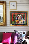 Modern artwork and gold-framed mirror on wood-panelled wall - floral and plain scatter cushions on sofa