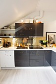 Modern attic kitchen with black and white fronts and shiny, gold, mosaic splashback