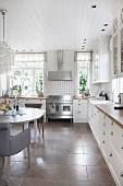 Essplatz mit Polsterstuhl in weisser Landhausküche, mit grossformatigen Steinbodenfliesen